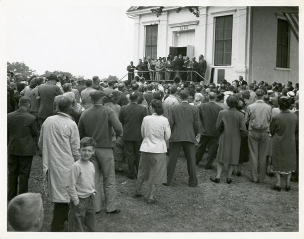 Official Swedish Delegation of the Swedish Pioneer Centennial gathered on the stoop of the Jenny Lind Chapel in Andover, Illinois, 1948. From the Allan Kastrup collection, Swenson Swedish Immigration Research Center.